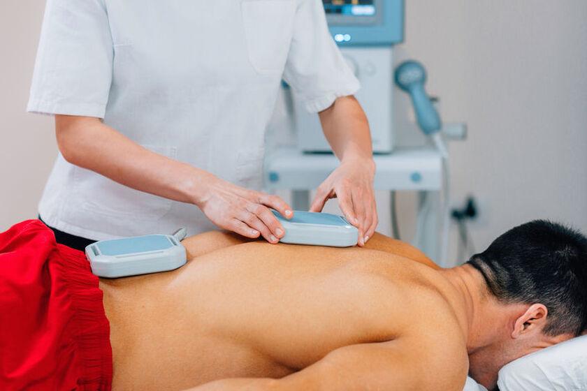 Osoba leżąca na brzuchu podczas zabiegu z użyciem pola magnetycznego