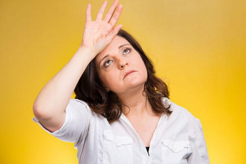 Zmęczona kobieta opierająca dłoń na czole