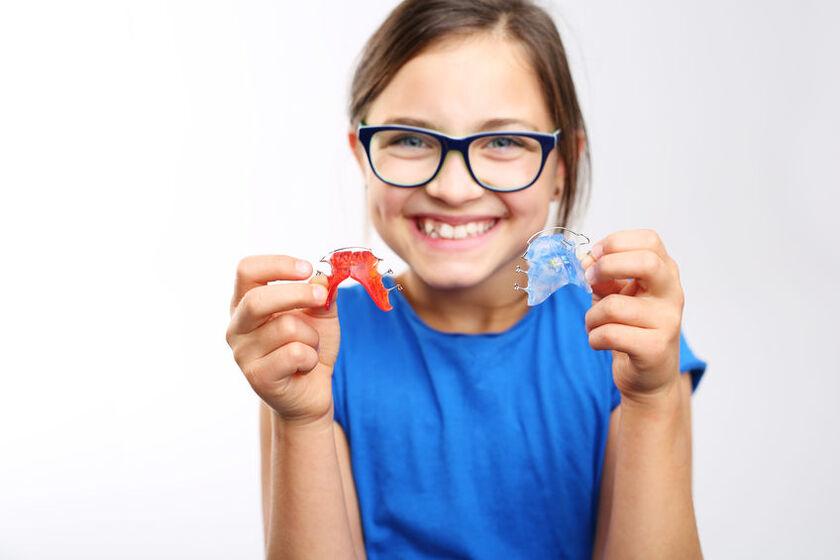 Dziewczynka pokazuje zdejmowany aparat ortodontyczny