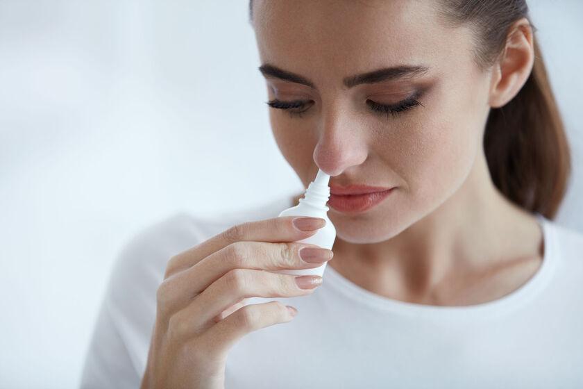 Kobieta wstrzykująca aerozol do nosa